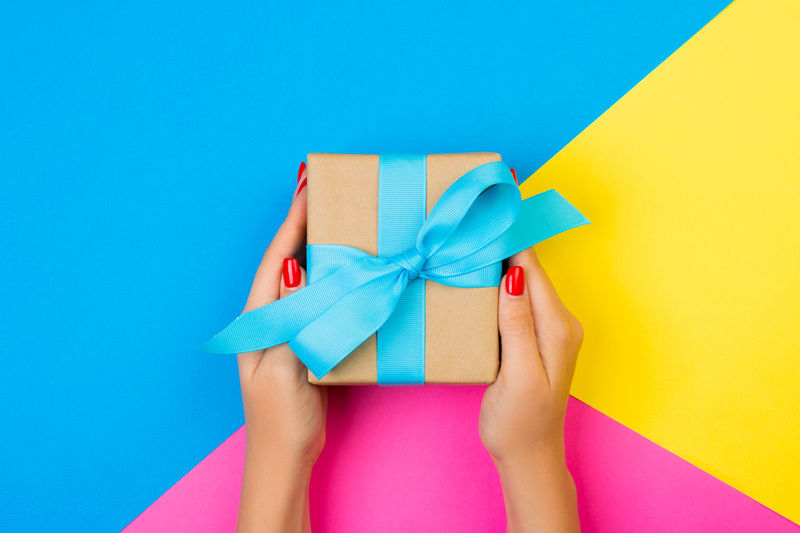 Directly above shot of cropped hands holding gift box on colored background