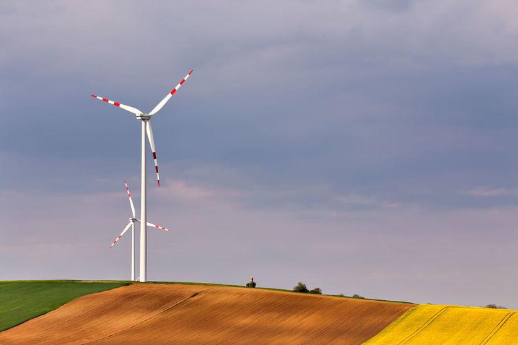 Windmills on hill against sky