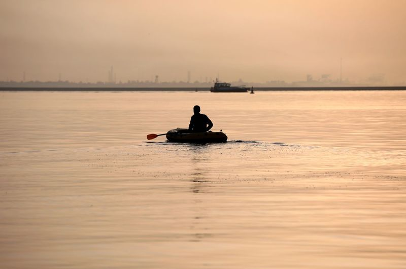 Silhouette mid adult man sitting in boat on sea against sky during sunset