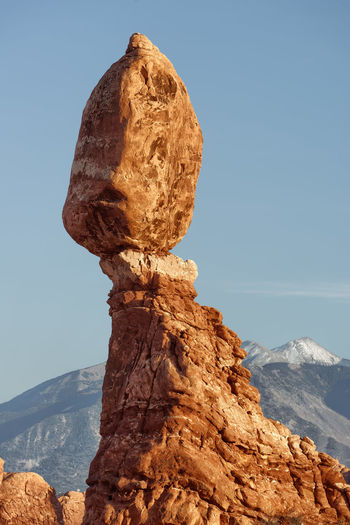 Rock formation by mountain against sky