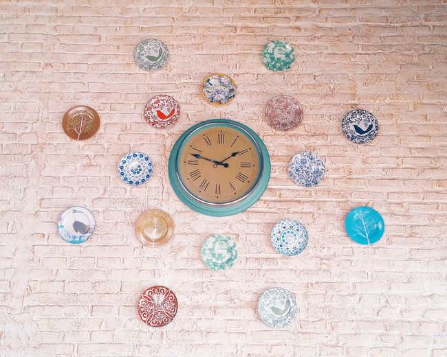 Low angle view of clock amidst colorful plates on wall