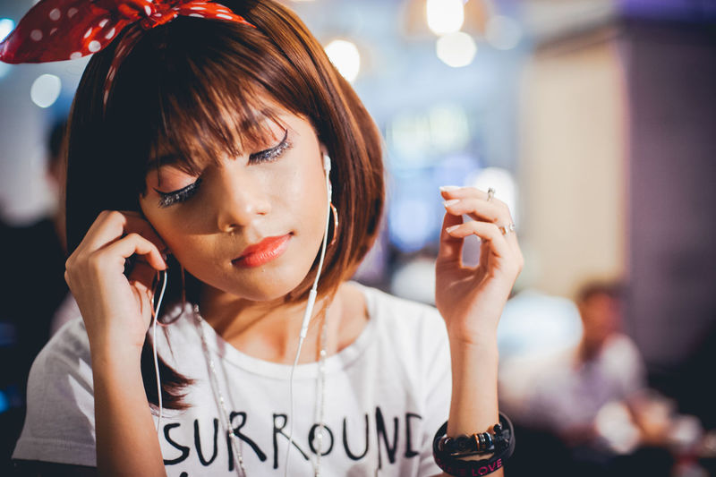 Adult Casual Clothing Close-up Communication Focus On Foreground Front View Headphones Holding Indoors  Listening Mobile Phone Night One Person People Portable Information Device Real People Smart Phone Technology Telephone Text Using Phone Wireless Technology Young Adult Young Women