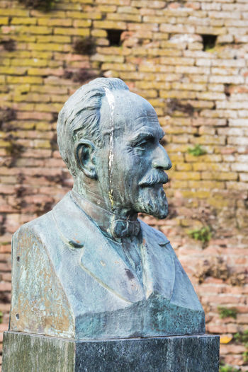 Old male statue against wall