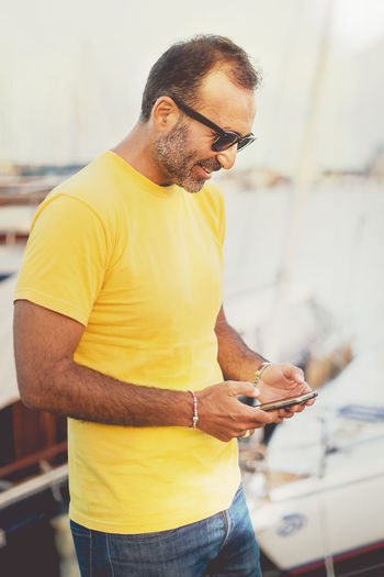 Man Using Phone While Standing At Harbor