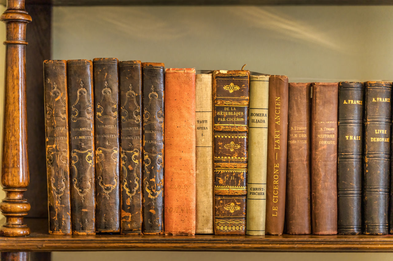 CLOSE-UP OF OLD BOOKS IN SHELF AT TEMPLE