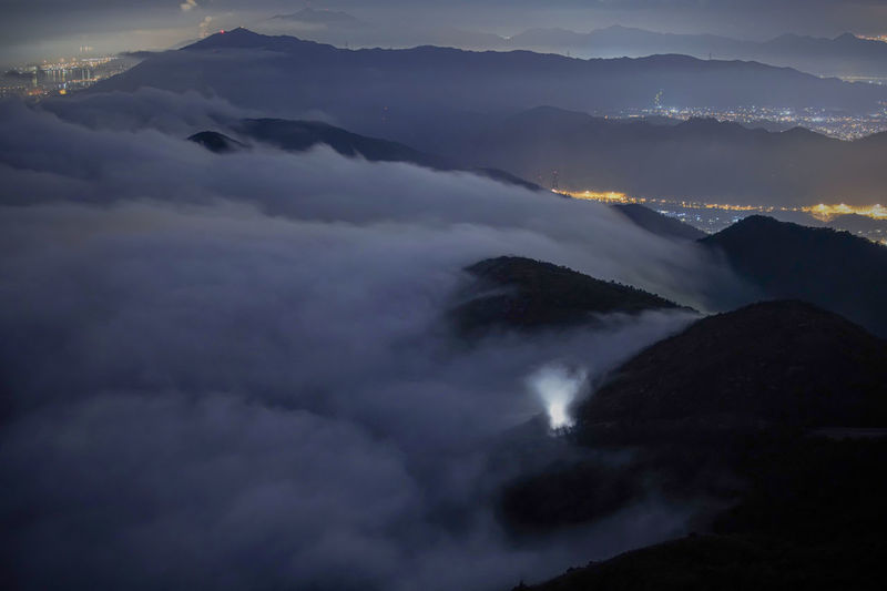 Scenic view of clouds covering mountain at dusk
