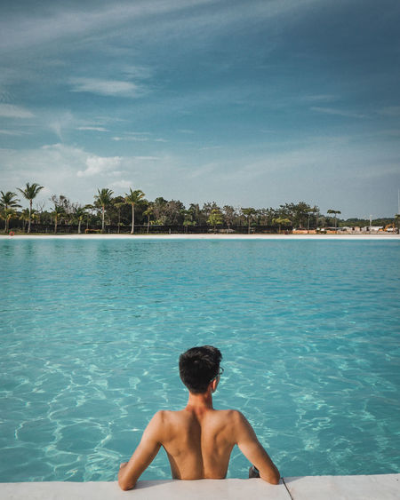 Rear view of shirtless man in infinity pool against sea