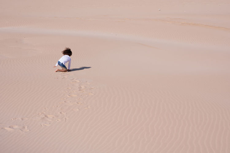 High angle view of boy crawling at desert