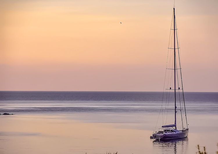 Sailboat in beach at sunset