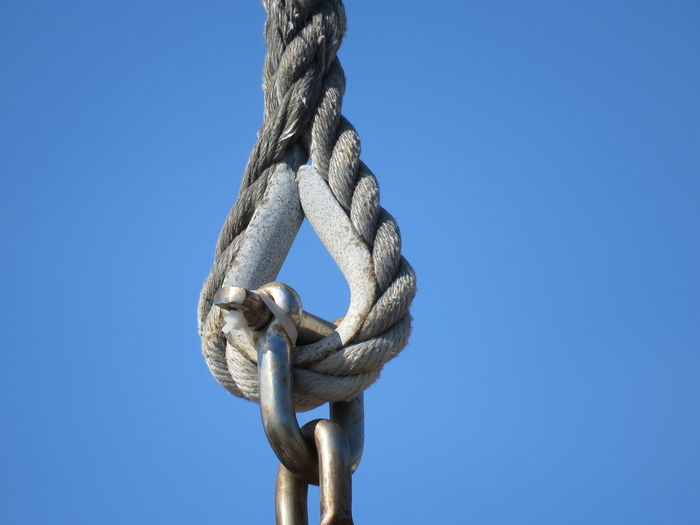 Low angle view of rope with hook against clear sky