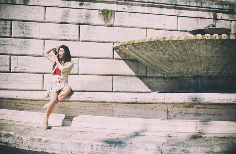 Young tourist woman taking photos in city vintage style Brick Wall Casual Clothing City Day Leisure Activity Outdoors Taking Photos Tourist Urban Vintage Photo Woman Young
