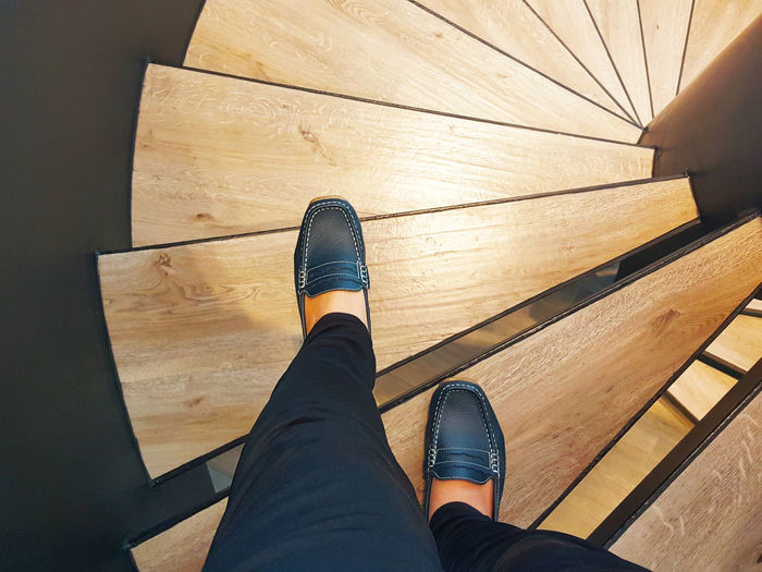 Low section of person on wooden spiral staircase