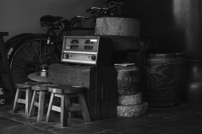 Antique radio, bicycle and others vintage goods still life Old Radio Vintage Indoors  Seat Chair No People Table Still Life Absence Wall - Building Feature Machinery Large Group Of Objects Stack Retro Styled Home Interior Empty Wood - Material Business Old Container Furniture