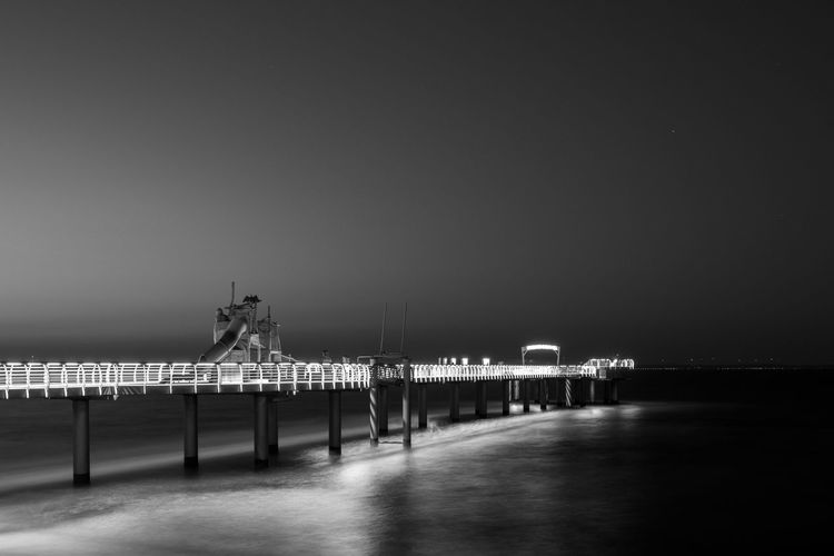 Blackandwhite Bkack And White Black And White Photography Pier Bridge Baltic Sea Timmendorfer Strand Niendorf, Ostsee Reflection Reflections In The Water Water Sea Night Nightphotography Architecture Illuminated Built Structure Sky No People Copy Space Nature Clear Sky Lighting Equipment Building Exterior Travel Destinations Street Light Outdoors Railing Building