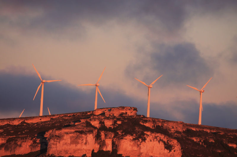 Low angle view of wind turbines on mountain against cloudy sky during sunset