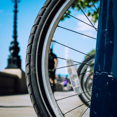Close-up of bicycle wheel against sky