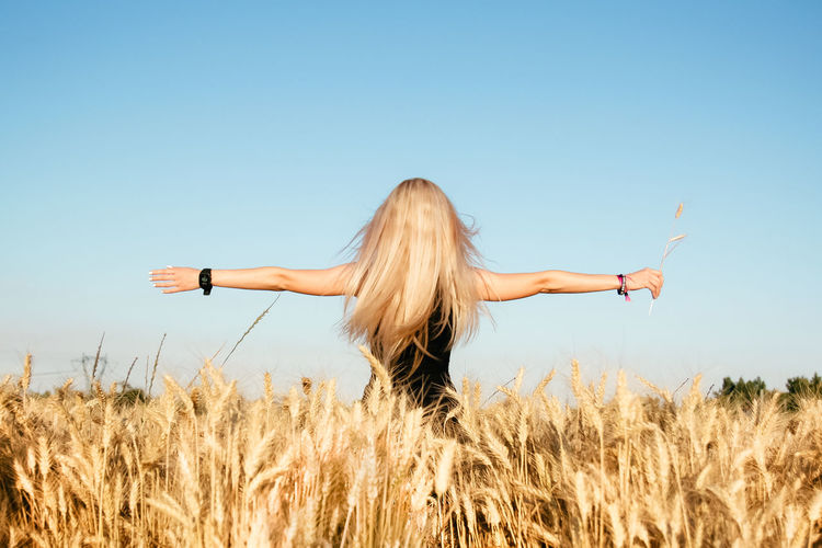 Blonde Girl Blond Hair Arms Outstretched Bio Blonde Clear Sky Clear Sky Energy Field From Behind Growth Harvest Lifestyles Long Hair Nature Outdoors Rear View Rear View Rural Scene Standing Summertime Sunny Wheat Inner Power International Women's Day 2019