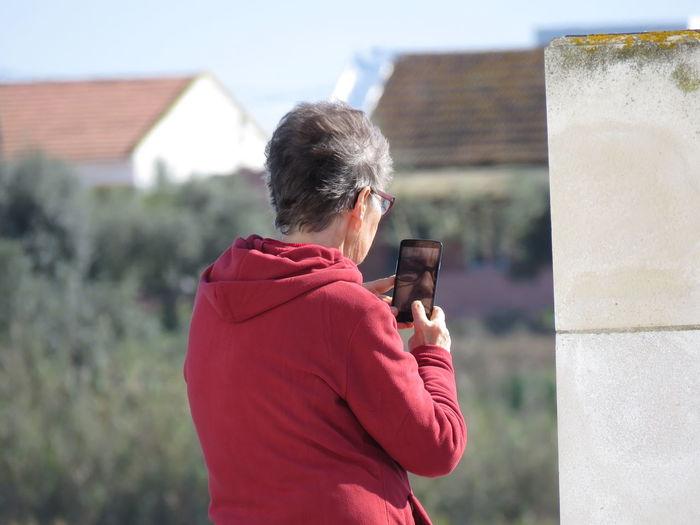 Rear view of senior man taking selfie on mobile phone