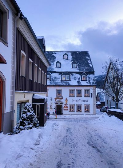 Snow covered houses by buildings against sky