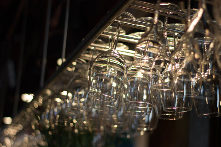 Low angle view of upside down wineglasses hanging on rack at bar