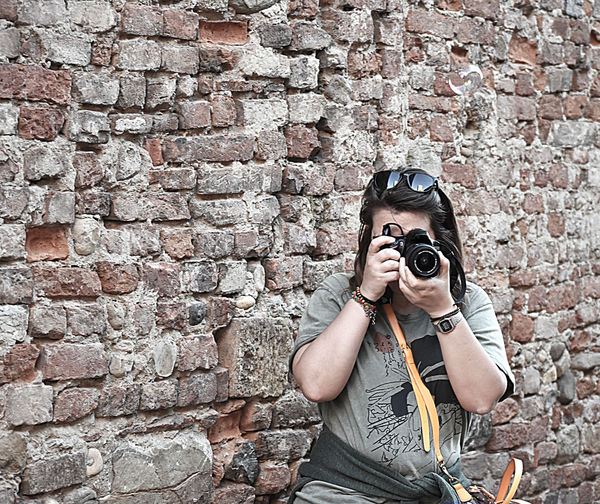 Woman photographing while standing against brick wall