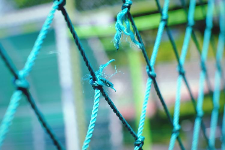 Close-up of rope tied to metal fence