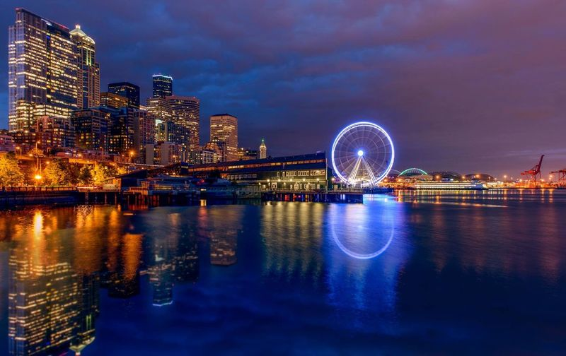 Ferris wheel by river in illuminated city against cloudy sky at night