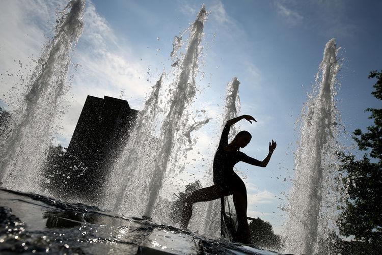 Full length of man splashing water against sky