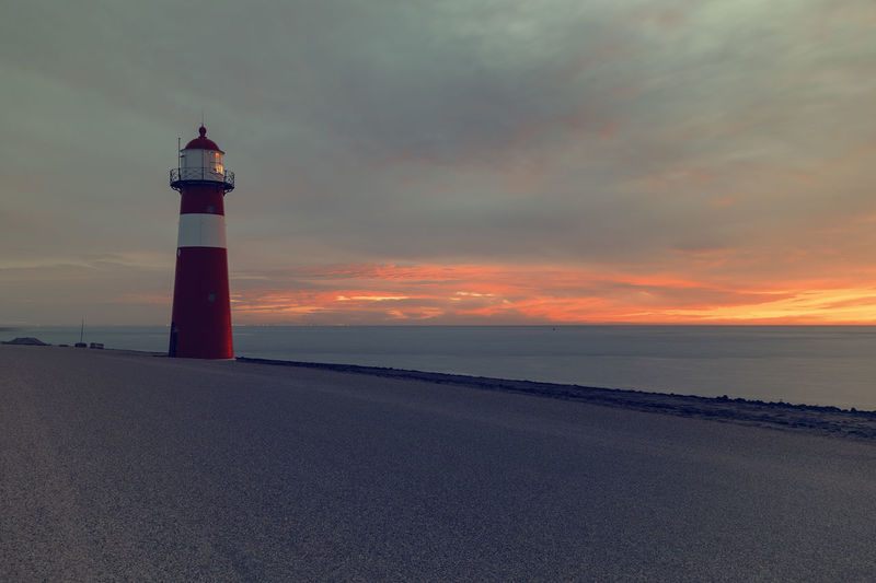 Lighthouse on the North Sea in the Netherlands North Sea Netherlands Art Guidance Tower Lighthouse Direction Sunset Sky Built Structure Architecture Sea Building Exterior Security Protection Safety Building Water Cloud - Sky Beach Land Nature Scenics - Nature No People Horizon Over Water Outdoors