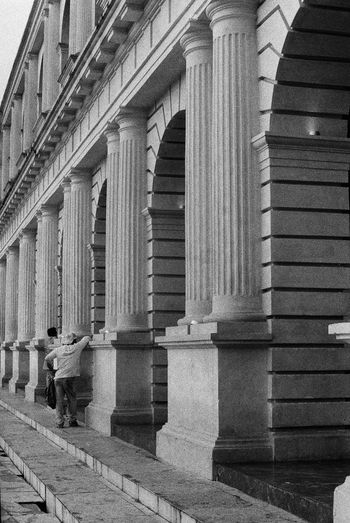 Rear view of man walking on building