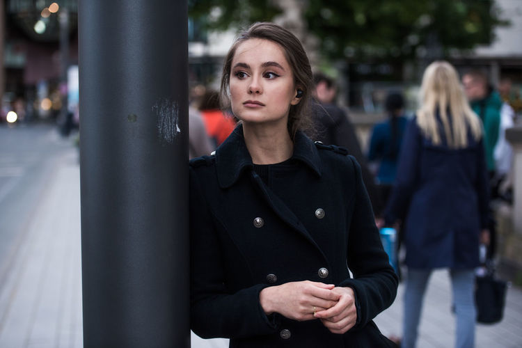 Young woman looking away while standing in city
