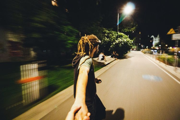 Cropped image of person holding man hand on road in city at night