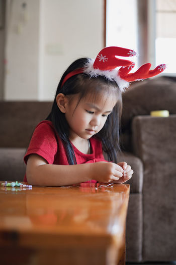 Cute girl making decoration on table