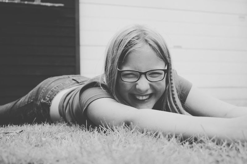 One Person Real People Lying Down Childhood Lying On Front Lifestyles Leisure Activity Girls Elementary Age Happiness Eyeglasses  Smiling Grass Wireless Technology Outdoors Blond Hair Day Close-up People