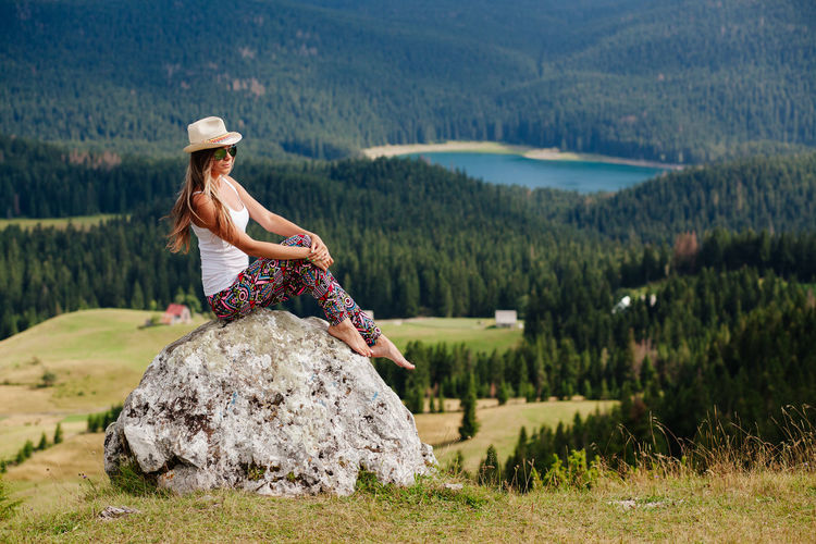 Full length of young woman relaxing on rock against mountain