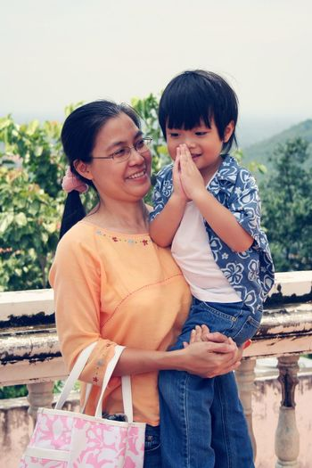 Smiling mother with son against sky