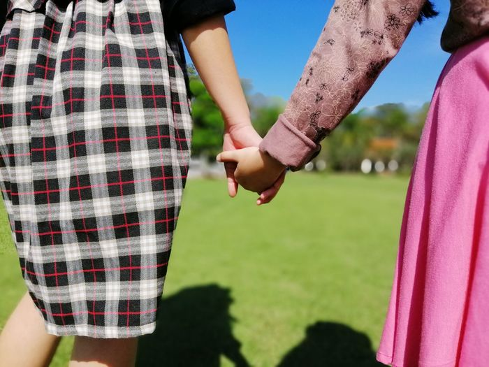Midsection of friends holding hands while walking on grassy field in park