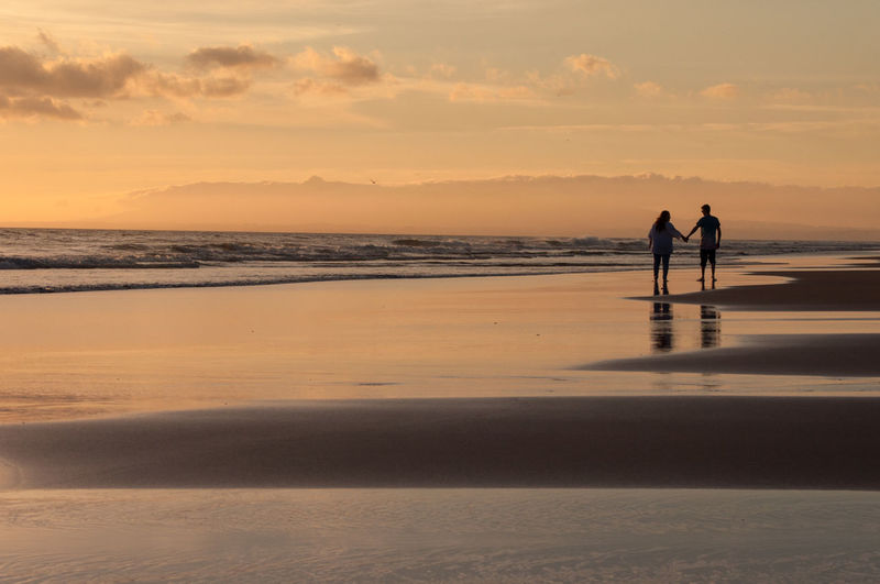 Silhouette Couple Holding Hands On Beach Against Sky During Sunset