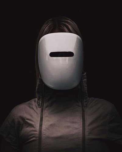 Close-Up Of Woman Wearing Mask And Hooded Jacket Against Black Background