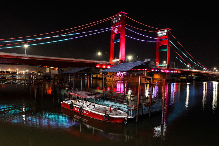 View of ampera bridge  over river at night