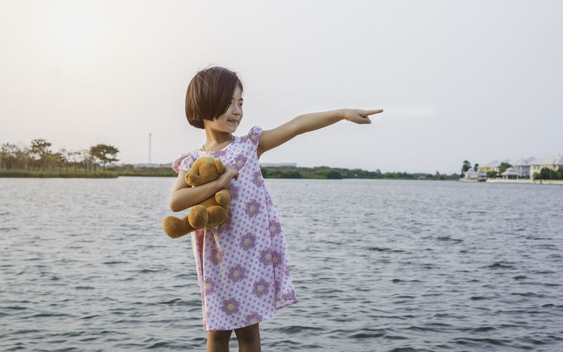 A portrait photo of a one happy girl standing by lake. She is holding cute little teddy bear in her hands. This cute little child is suitable for children in nature concept. Teddy Bear Daughter Childhood Child Outdoors Lake Nature Global Warming Travel Destinations Cute Asian  Small Little Light House Happy Vacations Village House Relaxing Family Time Kid Alone Holding Playful Smile Copy Space