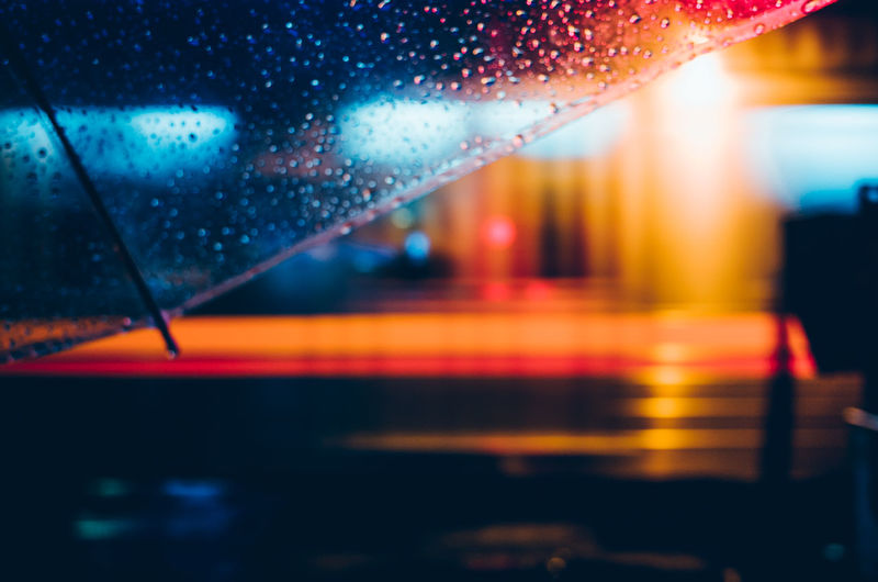 Cropped image of wet umbrella in city at night
