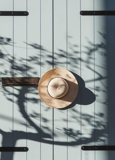 Hat hangin on old wooden door, pastel colored, neutrals.