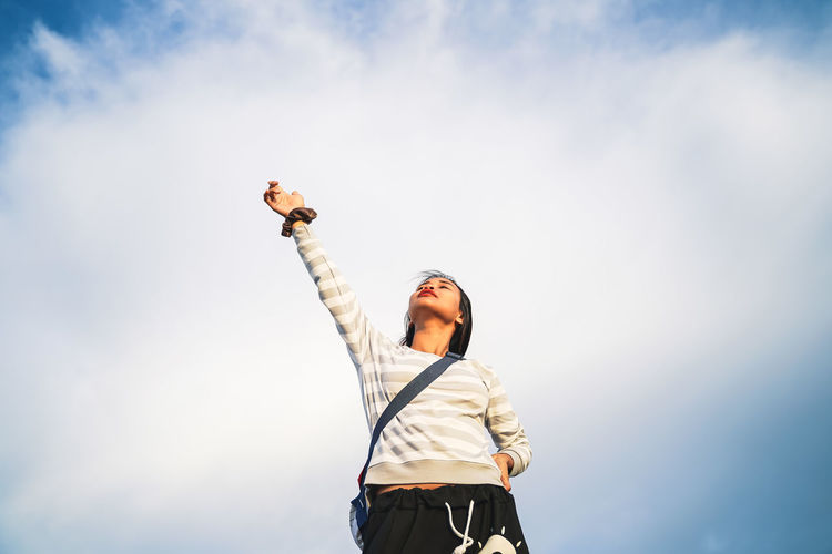 Low angle view of woman with hand raised standing against cloudy sky
