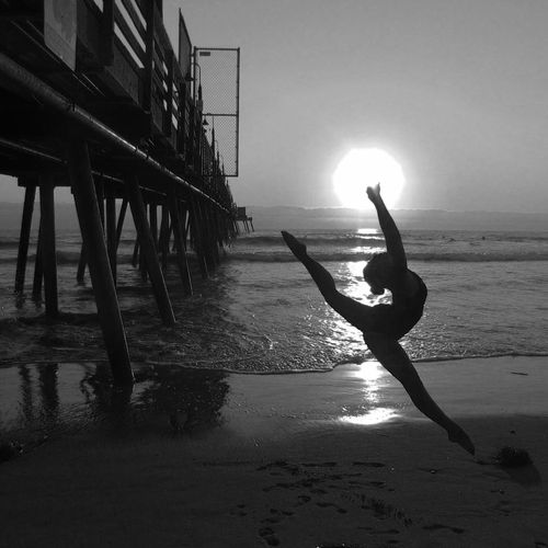 Silhouette woman dancing at beach by pier during sunset