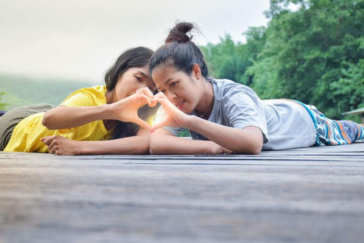Smiling women making heart shape lying on wood