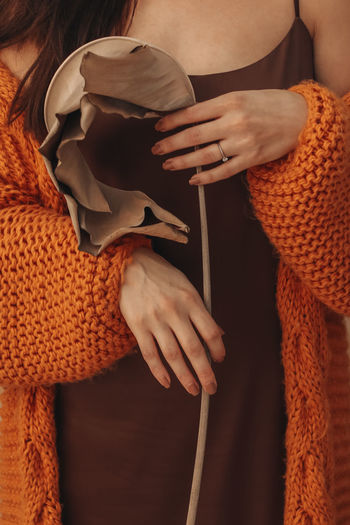 Cropped female body in an orange knitted cozy cardigan holding a beige dry plant. autumn