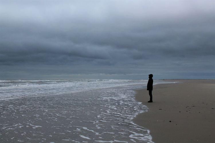 Side view of man standing on shore at beach against cloudy sky