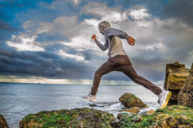 Full Length Of Man Running On Moss Covered Rock By Sea Against Cloudy Sky