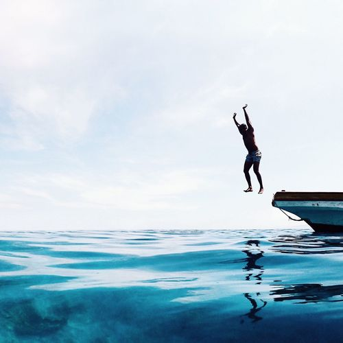 Man jumping in sea against sky